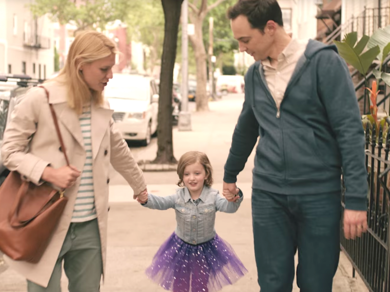 A still from the film 'A Kid Like Jake'. In a city-background with houses to the right and a car to the left, three figures: a blonde woman wearing a black and white striped t-shirt, blue jeans, and a beige coat, carrying a brown bag on her shoulder is holding a child's hand from the left. The child is wearing a purple, glittery tutu and a blue shirt. Their arms are outstretched and on the right side, held by a man wearing a peach shirt, blue hoodie and blue jeans. He has black hair. Both the man and the woman are looking at the child.