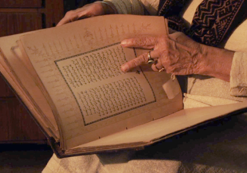 A photograph of an individual with a book. Their face is not visible. They are flipping through a seemingly old book, and are turning the page using two fingers. They are wearing a cream top with a brown scarf and a ring on their finger.