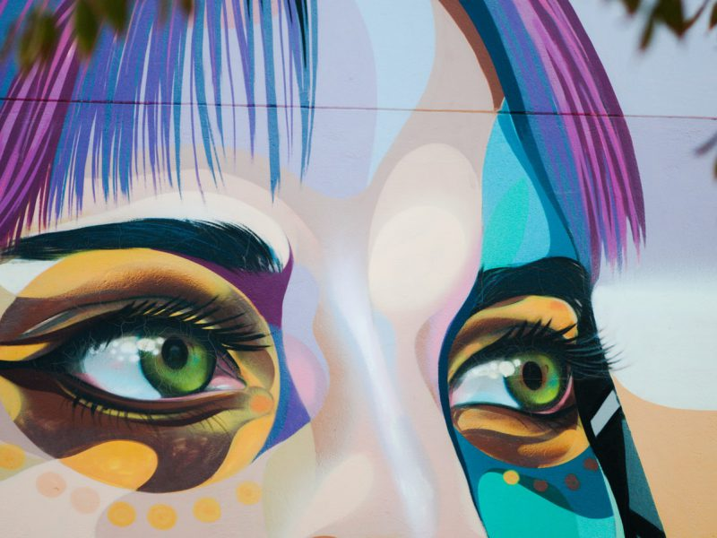 Wall-art of a face till the bridge of the nose. The face is coloured in peach, grey, and shades of blue. The eyes, green, are lined in black and have spots of yellow, brown, and blue colour around them. Under the left eye, there are yellow dots. The hair is streaked with purple and blue.