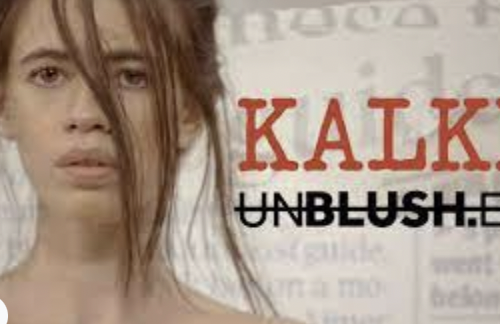 A screenshot of Kalki Koechlin's rendition of 'The Printing Machine'. The background has a fade-effect of newspaper headlines. To the left is Kalki's face till the beginning of her shoulders. She is looking directly at the camera. Her hair is tied with strands across her face. To the left, in big red lettering: KALKI an underneath it, in black and strikethrough: UNBLUSHED. 'BLUSH' is bold.