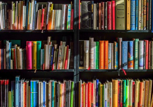A photograph of a book-shelf, brown-black, with differently coloured books.