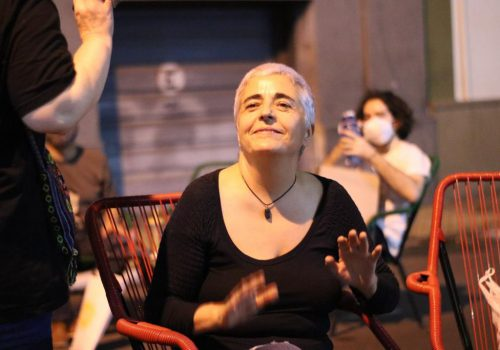 A photograph of a woman sitting indoors. She has cropped white-grey hair and is looking upwards. She is wearing a black full-sleeved top and her palms are open outwards. She is wearing a black necklace and is smiling. In front of her, a person is half-visible, clad in black, holding out their palms. There are red chairs on the side, and at the back, a person with black short hair, wearing a white top and mask, using a phone, is sitting.