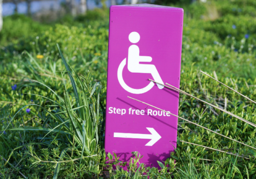 A photograph of a purple-coloured board on grass. The board, in white, has a symbol for a person using a wheelchair and underneath it, the typography: Step free Route. Below it is an arrow pointing to the right.