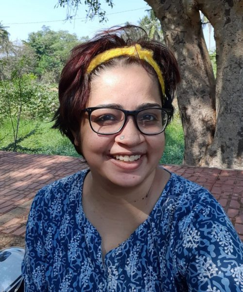 A photograph of disability rights activist Srinidhi Raghavan. She is wearing a blue top with a white pattern, black-rimmed spectacles, and a yellow hair-band.
